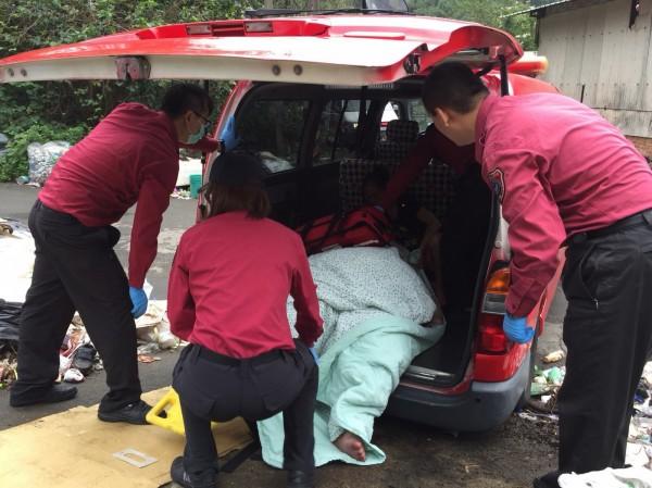 消防人員在搬運途徑鋪上厚紙板,以棉被充當墊被,拖行上勤務警備車送醫。(記者彭健禮翻攝)