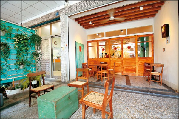 備料廚房前的騎樓,以傳統教師椅與舊式的木桌、木櫃等布置成開放式的座位區。(記者潘自強/攝影)
