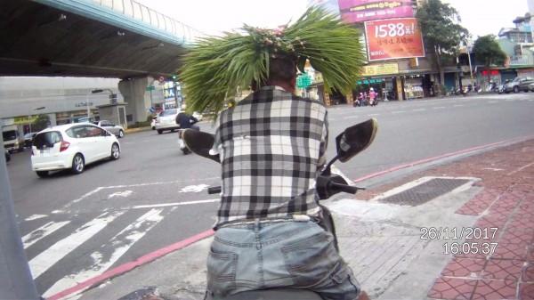 何男頭戴棕梠葉及麻繩編製的帽子騎機車上馬路,引來側目。(記者洪臣宏翻攝)
