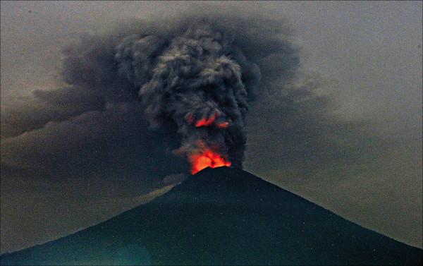 印尼當局已將峇里島阿貢火山的警戒程度調升至四級,並嚴防災情進一步擴大,持續兩個月的火山危機已重創峇里島觀光業,據報導,經濟損失約一.五億美元(約四十五.三億台幣)。圖為該火山廿七日的一景,冒出的煙霧、火焰籠罩在火山口上空。(美聯社)
