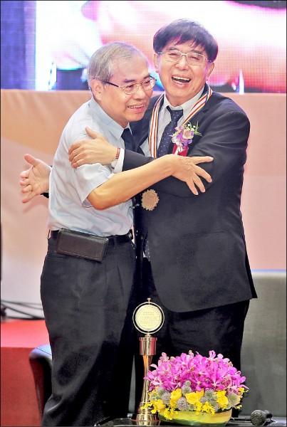 李伯璋(右)榮獲醫療奉獻特殊貢獻時,與哥哥李伯皇(左)相擁。(李伯璋提供)