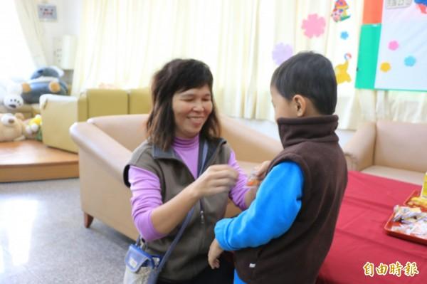 寄養媽媽陳明君悉心呵護浩浩,幫他穿上保暖外套。(記者鄭名翔攝)