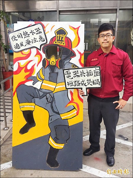 黃思銘與他第一個大型作品-消防員造型看板。(記者曾健銘攝)