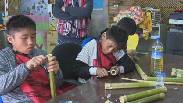仁愛鄉廬山部落學童埋首利用竹子製作傳統樂器「獵首笛」。(記者佟振國翻攝)