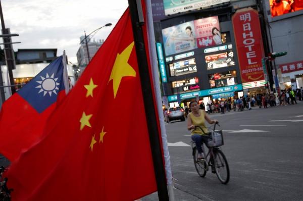 中國全國政協主席俞正聲,以及外交部發言人陸慷今(11)日都表示,北京將堅持「和平統一、一國兩制」方針。圖為中國國旗與台灣國旗同時出現在台北街頭。(路透)