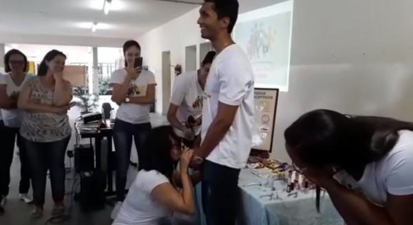 一名大學女講師請一位男同學夾緊教學用的塑料陰莖,自己則蹲下使用嘴巴將其套上保險套。(圖擷取自影片)