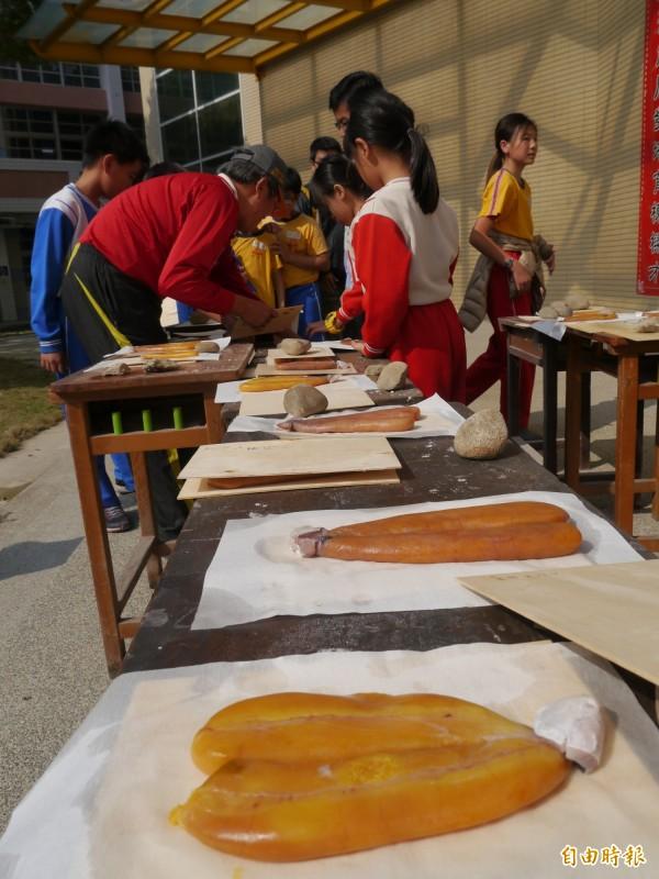 大秀國小學童製作黃澄澄的烏魚卵排放在桌面曝曬。(記者張軒哲攝)