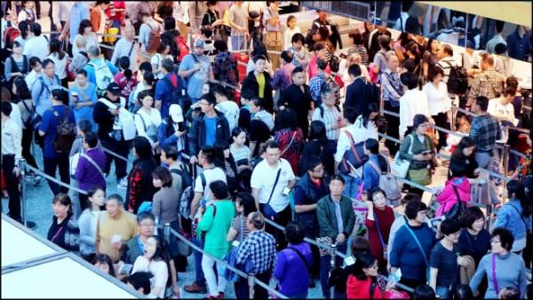 又有旅行社遭勒令停業!圖為出國旅客在桃機大排長龍等候查驗通關的資料畫面。(資料照)