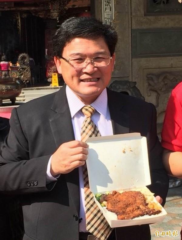 彰化市長邱建富拿著市價75元的排骨便當直呼「高檔」,呼籲民眾踴躍索取。(記者湯世名攝)