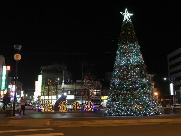 後龍鎮公所在後龍火車站前廣場架設一座7公尺高耶誕樹,夜晚點亮璀璨燈光,為小鎮增添溫馨氣氛。(後龍鎮公所提供)