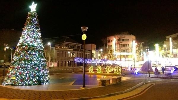 後龍鎮公所在後龍火車站前廣場架設一座七公尺高耶誕樹,夜晚點亮璀璨燈光,為小鎮增添溫馨氣氛。(後龍鎮公所提供)