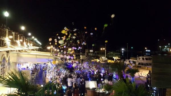 淡水漁人碼頭商家推出喜迎跨年活動,31號當晚會在店門口發放氣球。(新北市漁業及漁港事業管理處 提供)
