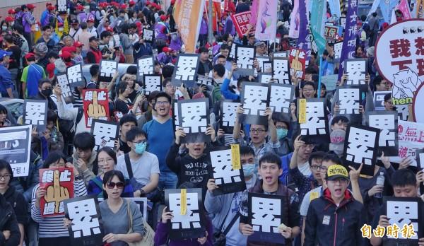 勞工團體23日舉行「反對勞基法修惡大遊行」,群眾高舉手中「終止過勞」、「累」標語高呼口號。(記者劉信德攝)
