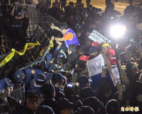 勞團遊行入夜時再爆發衝突,有民眾翻上拒馬濺血。(記者黃耀徵攝)