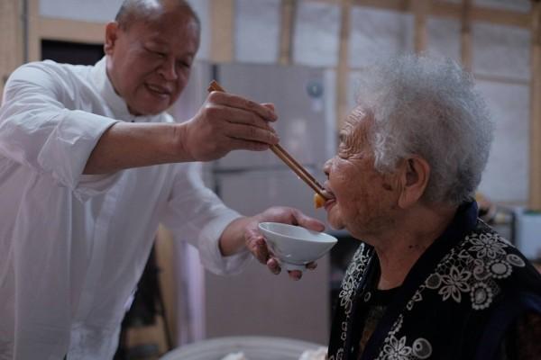 嘉義縣議長張明達餵93歲的母親張林醋,享天倫之樂。(張明達提供)