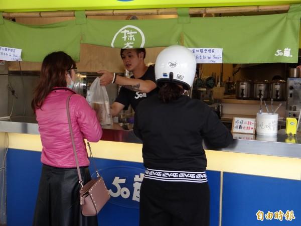 少數消費者向茶飲店加購塑膠袋包裝購買的飲料。店家貼出公告不再提供免費塑膠袋。(記者王俊忠攝)