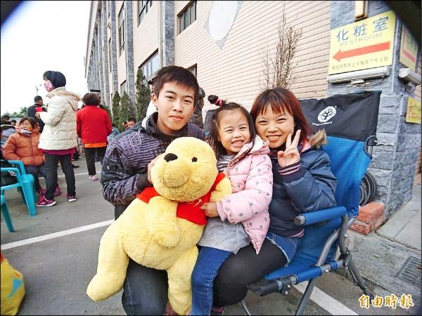通霄鎮拱天宮昨天開始受理點斗燈登記,來自彰化市的張惠玲(右)與家人排了3天3夜拔得頭籌。(記者張勳騰攝)