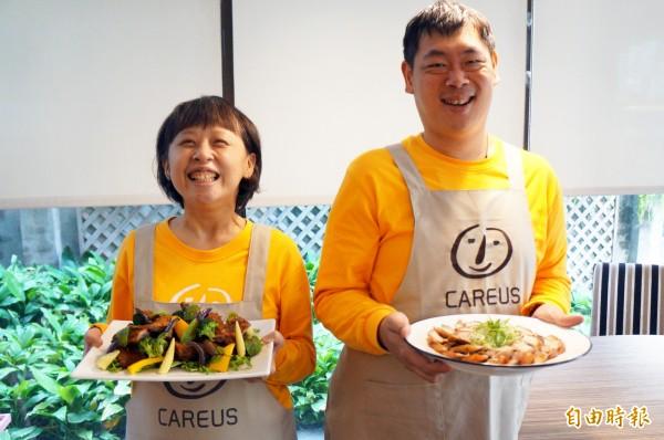 憨兒小儀(左)與阿宏一同展示年菜。(記者張忠義攝)