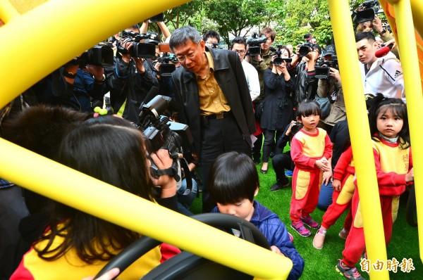 台北市長柯文哲說大稻埕煙火節有編預算,但被議員刪掉。圖為柯文哲今參加4座共融式遊戲場啟用記者會,好奇地看小朋友操作遊戲設施。(記者王藝菘攝)