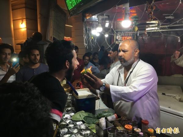 印度街頭流行的火燒檳榔,店家會在檳榔上點火後硬塞進顧客嘴裡。(印度尤提供)