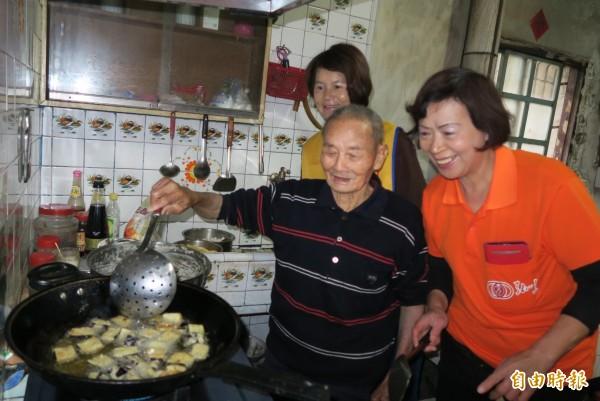 陳照阿公發揮拿手菜油炸茄子,讓大家「呷茄會秋條」(台語)。(記者陳冠備攝)