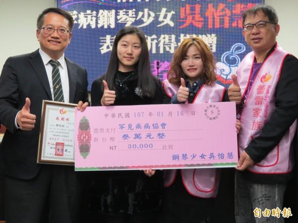 罕病鋼琴少女吳怡慧(左二)捐出演出所得給罕見疾病雷特氏症病友關懷協會。(記者蔡文居攝)