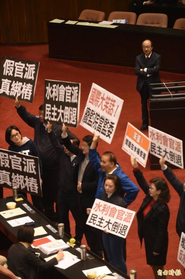 二讀完成後,國民黨立委齊聚,高舉標語表達「反官派」的立場,民進黨團總召則在後旁觀。(記者劉信德攝)