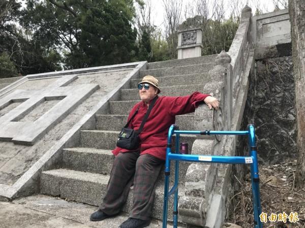 張日明因為年事已高,無力踏上陡峭階梯,他隻身坐在階梯上輕嘆。(記者沈佩瑤攝)