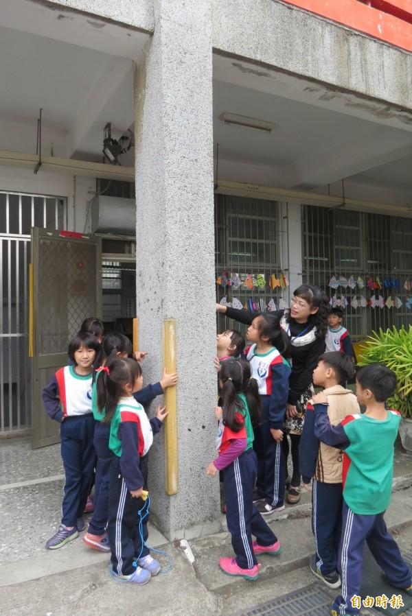 不少學生不捨地抱抱老校舍柱子。(記者蘇孟娟攝)