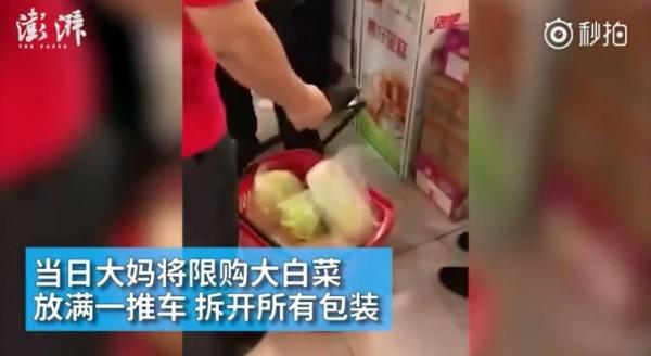 中國大媽將白菜包裝撕開、塞滿推車。(圖擷取自《澎湃新聞》微博)