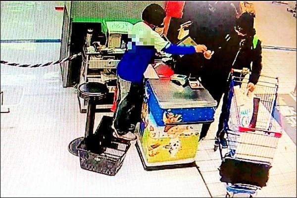 竊賊將酒藏在購物推車下方的黑袋子(畫紅圈處),以為神不知鬼不覺,卻被眼尖的店員盯上。(記者姚岳宏翻攝)