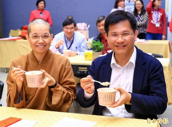 佛光山中區總住持覺居法師(左)與台中市長林佳龍共享臘八粥。(記者張菁雅攝)