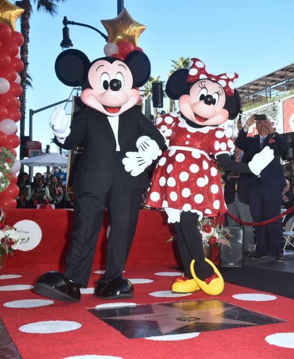 米妮週一身穿招牌紅底白點裙及黃色高跟鞋,和米奇一起現身星光大道的慶祝活動。(法新社)