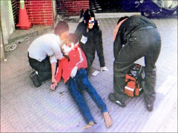 吳男受傷後帶著陳女(長髮)逃往警所求救後倒地,女警協助救護人員。(記者陳恩惠翻攝)