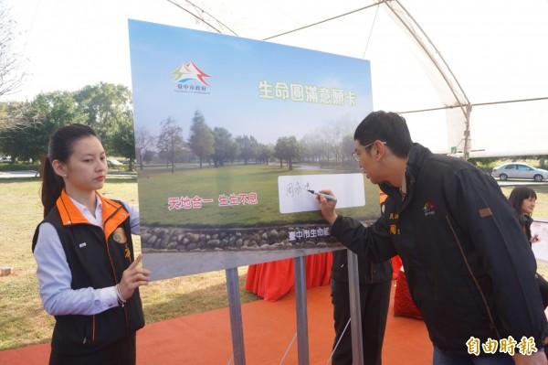 民政局長周永鴻在會中簽署「生命圓滿意願卡」。(記者歐素美攝)