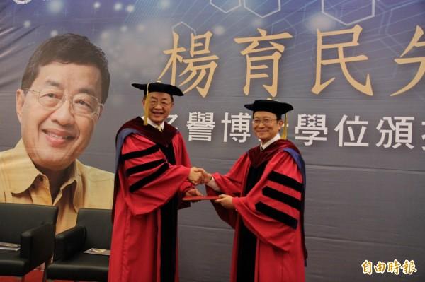 交通大學校長張懋中(右)頒發名譽博士給交大校友楊育民(左),表彰其在科技與生物產業的貢獻與成就。(記者洪美秀攝)