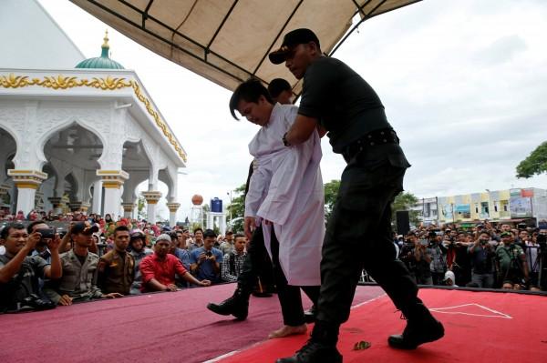 印尼當局今日表示,亞齊省警方於上週五逮捕了12名跨性別女性,「教育」他們如何做個男人。圖為去年1名男同性戀者遭到亞齊省警方鞭刑。(資料照,路透)