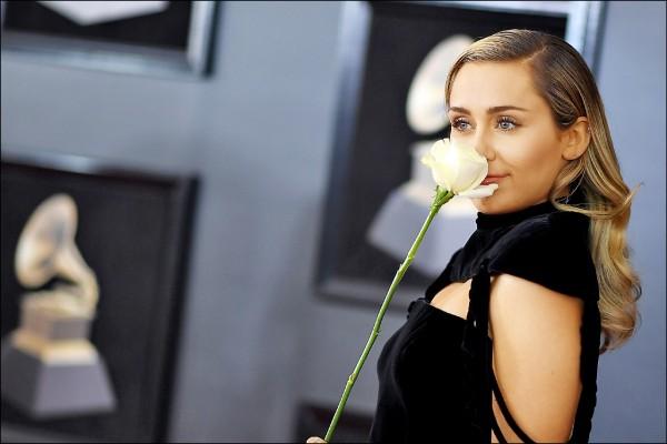 葛萊美獎昨頒獎,麥莉等樂壇明星走紅毯時紛紛配戴白色玫瑰,爭取性別平權。(法新社)