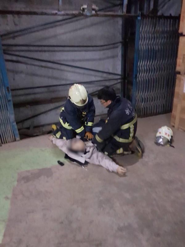 消防人員將不慎墜落電梯井的黃男救出。(記者曾健銘翻攝)