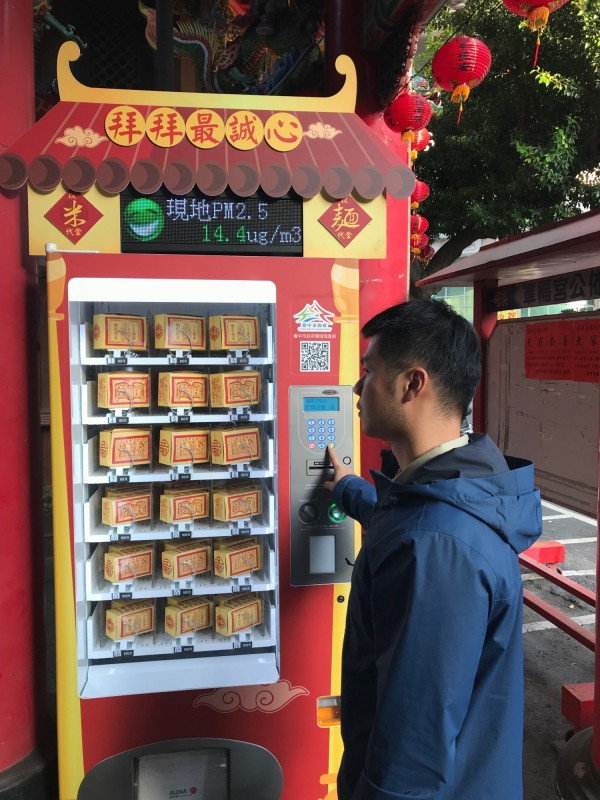 環保局在軍福宮示範設置「平安祈福販賣機」,信徒可投幣購買,上方還設有即時電子空品看板顯示廟裡PM2.5濃度。(記者蔡淑媛翻攝)