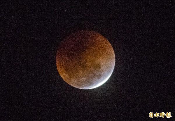 百年奇象「天狗吞藍月」,進入「生光」階段逐漸「復圓」。(記者張忠義攝)