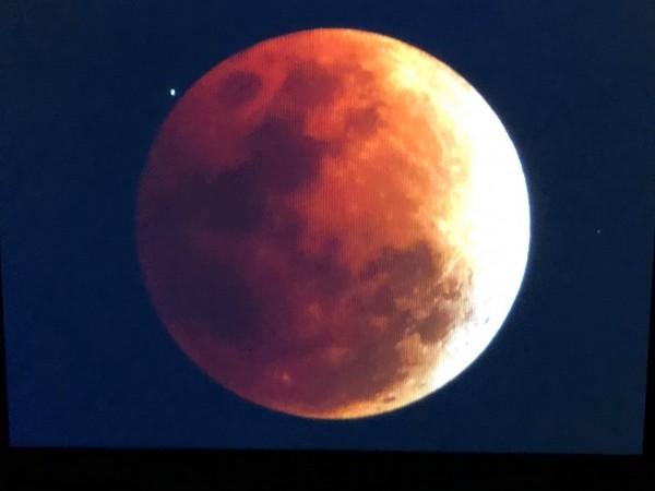 「紅色超級藍月」在墾丁現身,守候在鵝鑾鼻的民眾成功拍到這個百年天文奇景。(記者蔡宗憲翻攝)