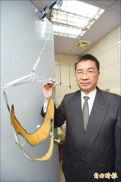徐國勇在辦公室裡擺了一台朋友送他的簡易式頸椎牽引器,一有空就拉脖子舒緩頸椎。(記者方賓照攝)