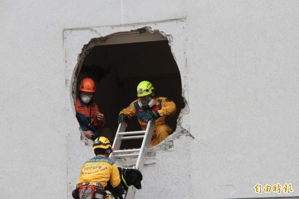 搜救人員帶著搜救犬繞到統帥飯店另一端窗口進入,另覓搜救途徑。(記者林欣漢攝)