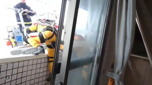 特搜隊員搭乘雲梯車冒險進入雲堤大樓8樓。(記者湯世名翻攝)