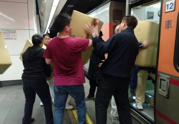 旅客們齊心協力傳遞物資。(擷取自「慈濟@臺北」臉書粉專)