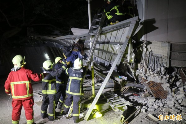 消防救難人員搜救受困在倒塌大樓內的民眾。(記者王錦義攝)