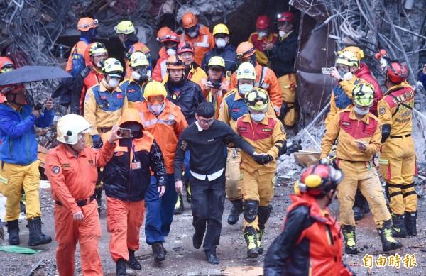 統帥飯店現場下午3時傳出好消息,飯店員工梁書瑋受困15小時後,在救難人員攙扶下步出建築物。(記者羅沛德攝)