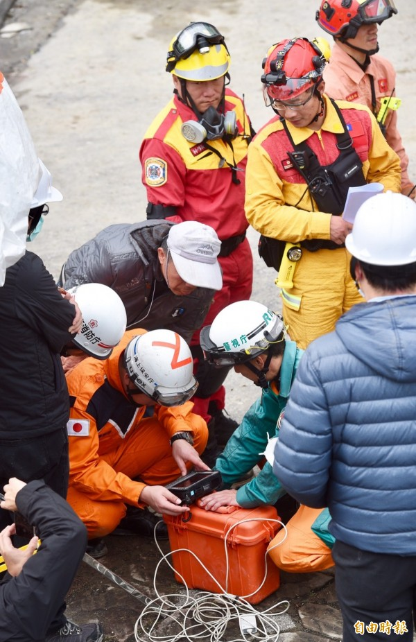 日本救難人員以精密儀器尋找生命跡象,期盼有奇蹟發生。(記者羅沛德攝)