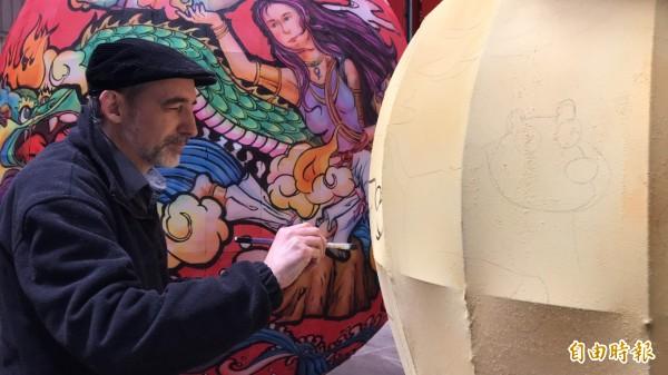 義大利籍插畫家朱米傑(STEFANO    MISESTI)正在創作「就柿旺」,作為今年新埔花燈迎天穿的主燈。(記者黃美珠攝)